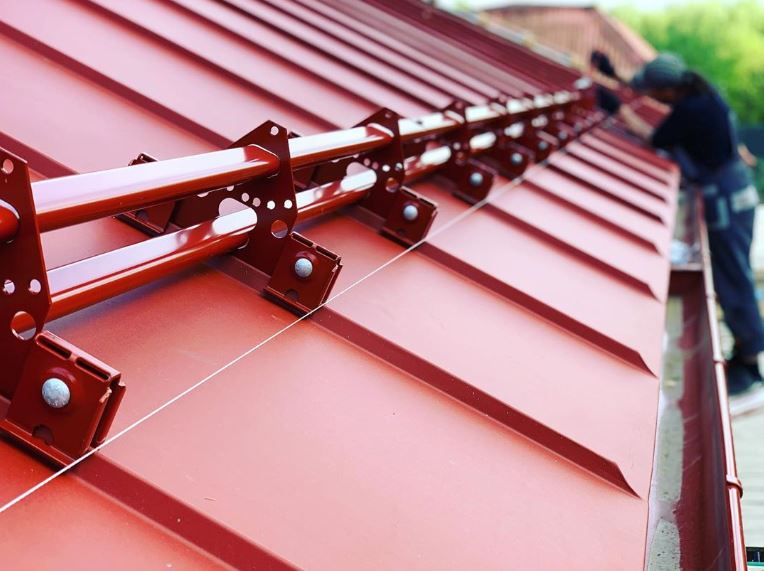 Snow guards for standing seam metal roofs