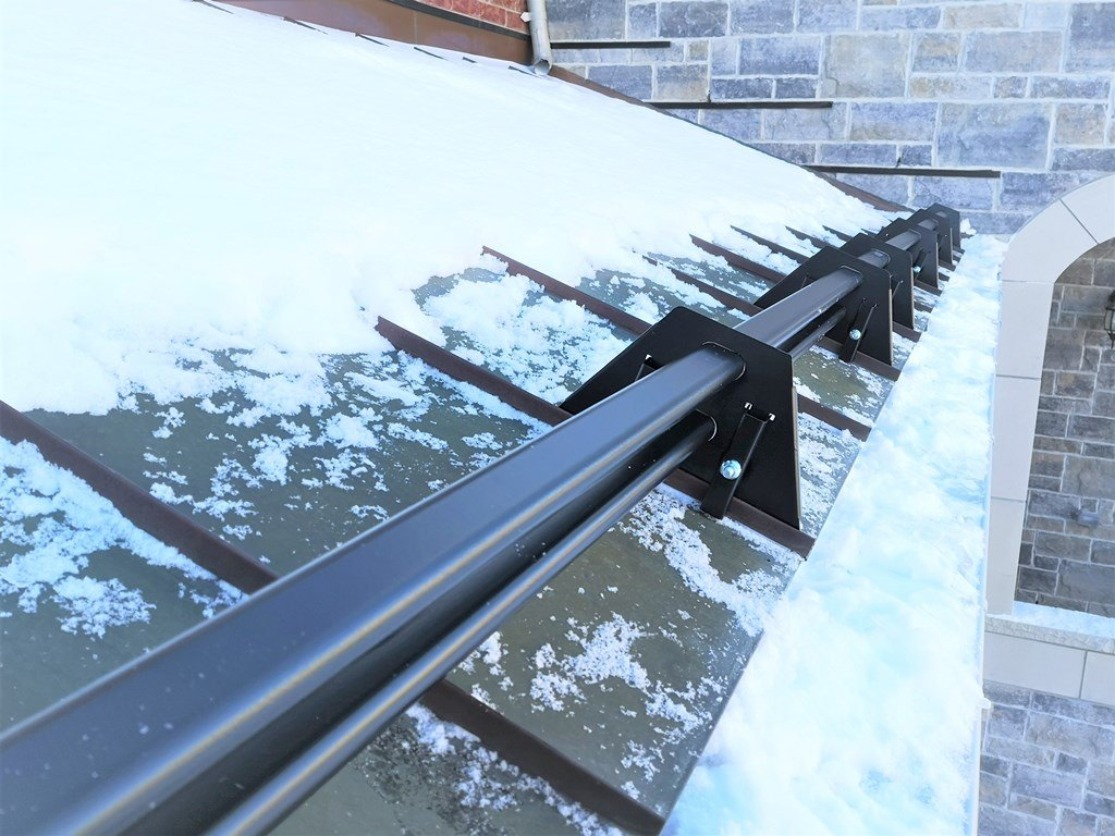 Snowguards on metal roof above garage door
